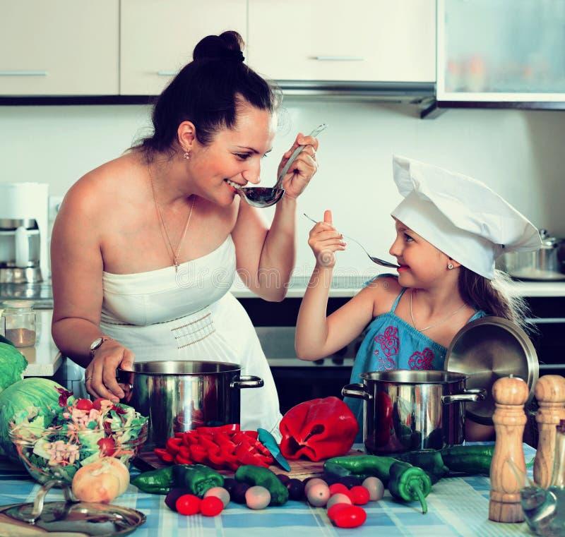 Vrolijk gelukkig meisje die moeder helpen aan kok royalty-vrije stock foto