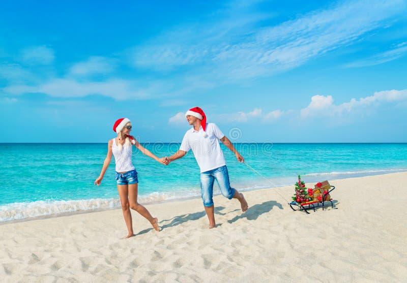 Vrolijk glimlachend jong paar die in rode Kerstmanhoeden bij tropisch oceaan zandig strand met sleeën verfraaide spar en gouden v stock fotografie