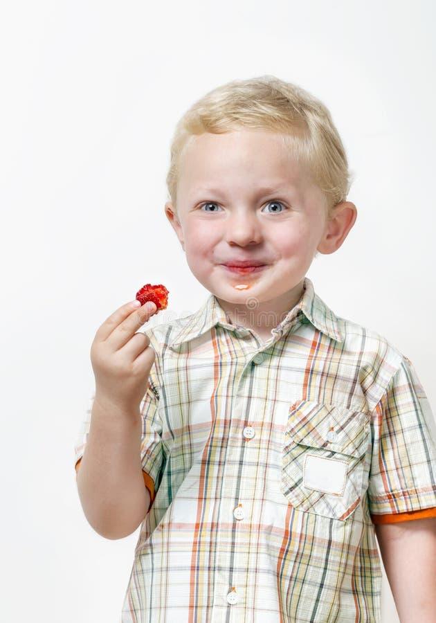 Vrolijk glimlachend weinig jongen die rode aardbei eten royalty-vrije stock afbeeldingen