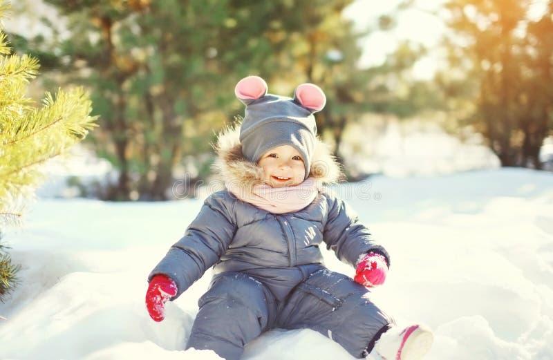 Vrolijk glimlachend weinig kind die op sneeuw in de winter spelen stock foto's