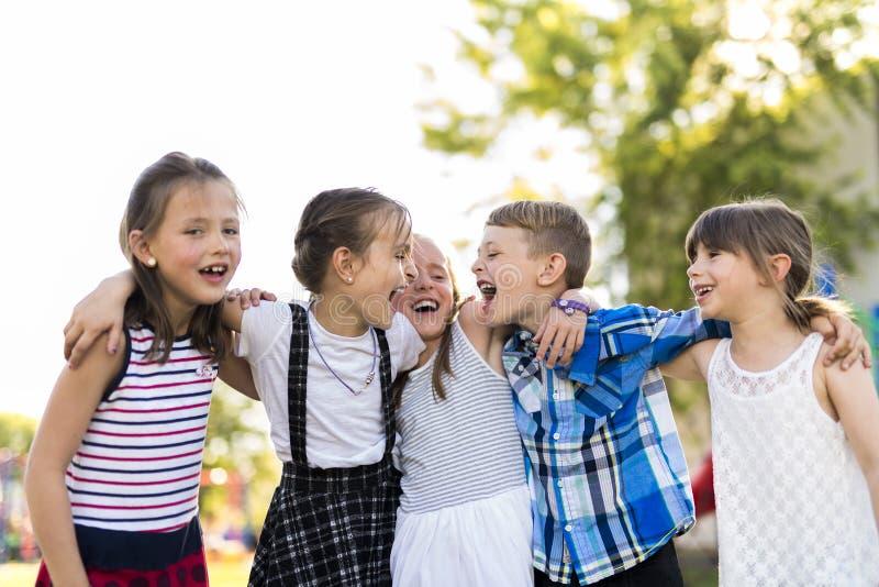 Vrolijk het kindspel van de schoolleeftijd op speelplaatsschool stock foto