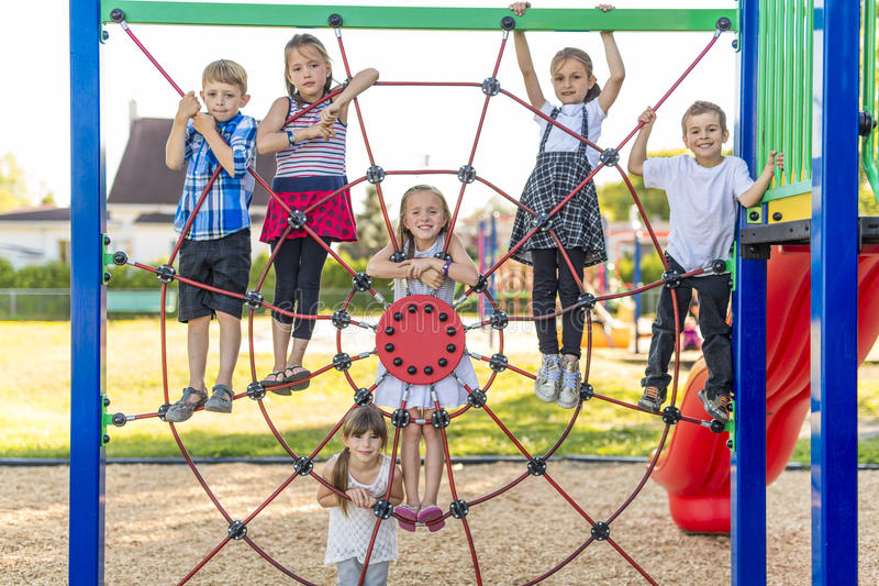 Vrolijk het kindspel van de schoolleeftijd op speelplaatsschool stock afbeelding