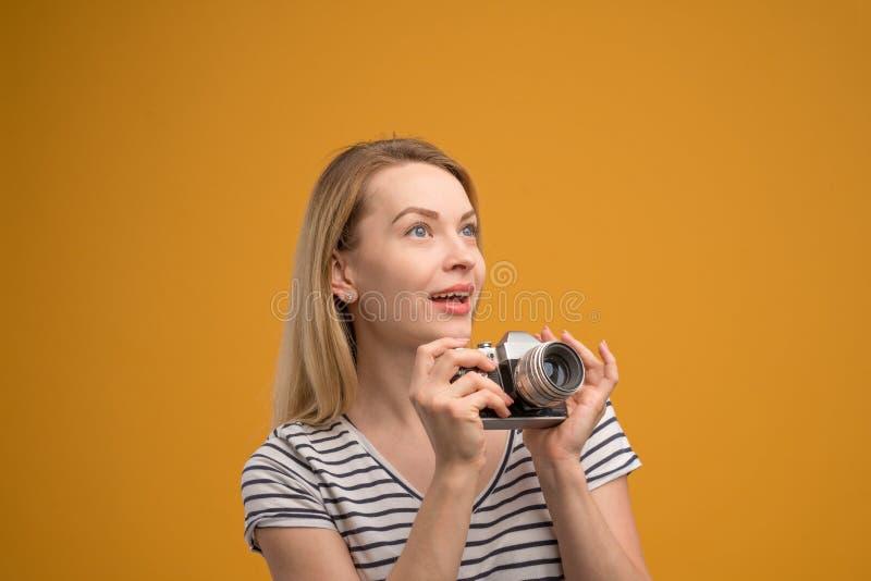 Vrolijk hipstermeisje met retro camera op een gele achtergrond stock foto