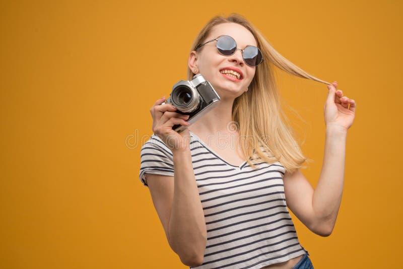 Vrolijk hipstermeisje met retro camera op een gele achtergrond royalty-vrije stock fotografie