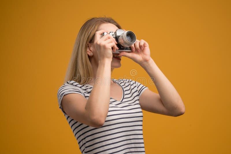 Vrolijk hipstermeisje met retro camera op een gele achtergrond royalty-vrije stock afbeeldingen