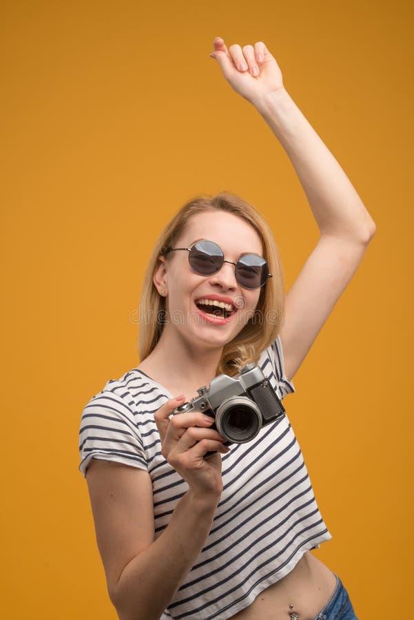 Vrolijk hipstermeisje met retro camera op een gele achtergrond royalty-vrije stock foto