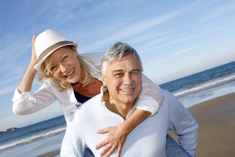 Vrolijk hoger paar die in de zomer op het strand lopen stock foto's