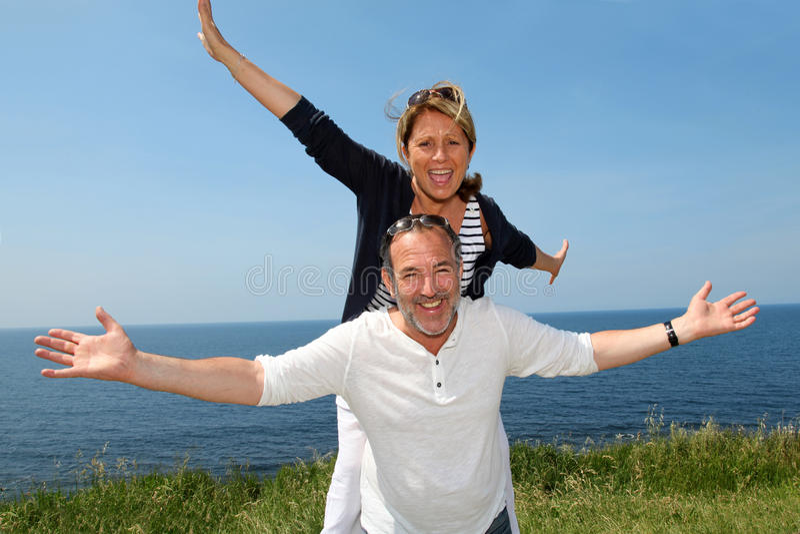 Vrolijk hoger paar die zich door de kust bevinden royalty-vrije stock foto's