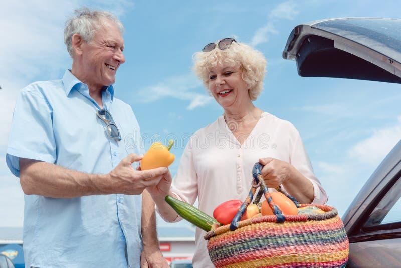 Vrolijk hoger paar gelukkig voor het kopen van verse groenten van Th royalty-vrije stock afbeeldingen