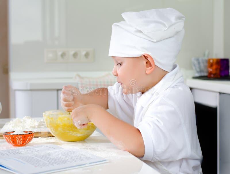 Vrolijk jong chef-kokbaksel in de keuken stock afbeelding