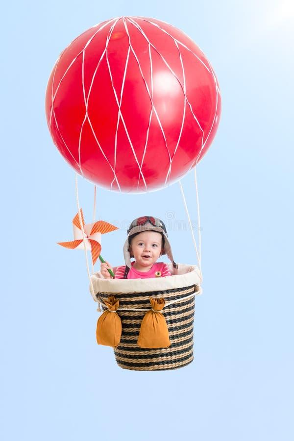 Vrolijk jong geitje op hete luchtballon in de hemel royalty-vrije stock afbeelding
