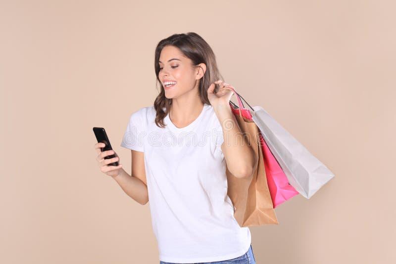 Vrolijk jong meisje in basiskleren die mobiele telefoon met behulp van terwijl het houden van het winkelen die zakken over beige  stock afbeeldingen