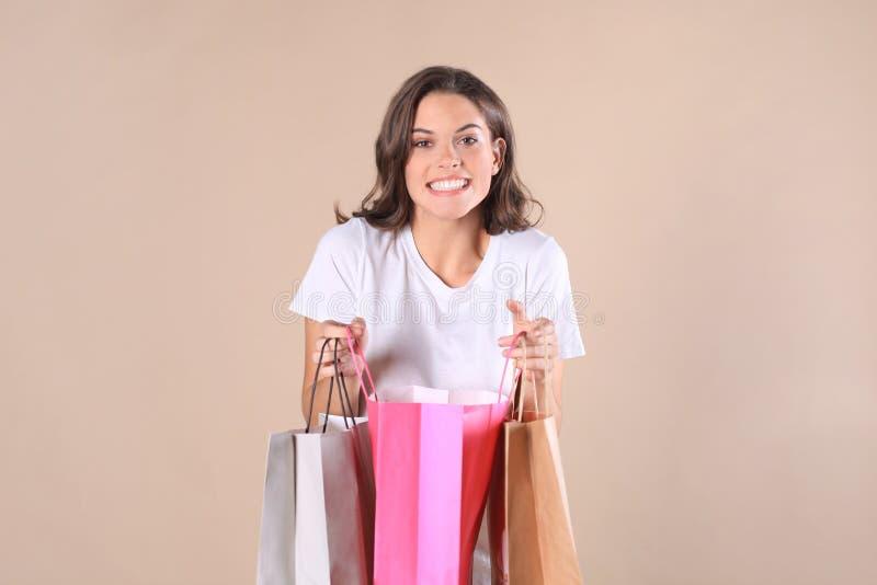 Vrolijk jong meisje in basiskleren terwijl het houden van het winkelen die zakken over beige achtergrond worden geïsoleerd stock afbeelding