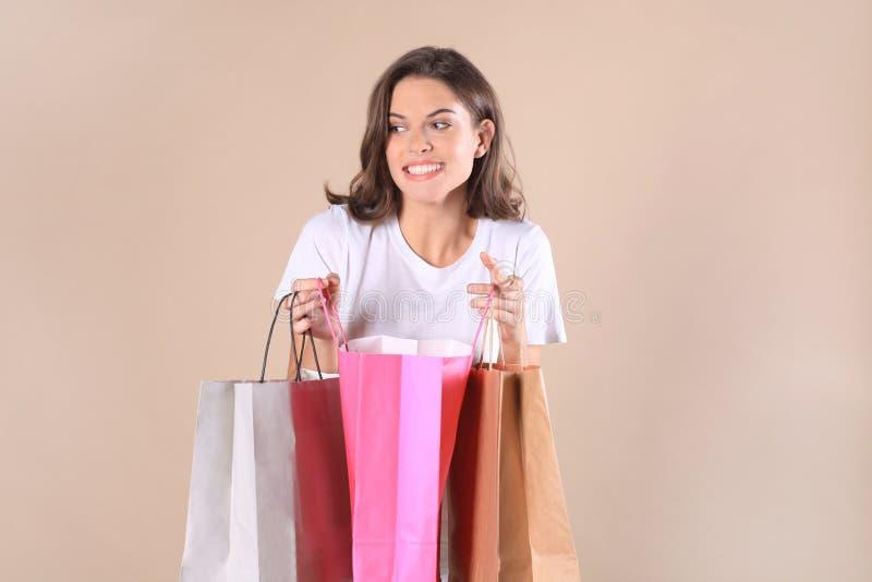 Vrolijk jong meisje in basiskleren terwijl het houden van het winkelen die zakken over beige achtergrond worden geïsoleerd stock foto