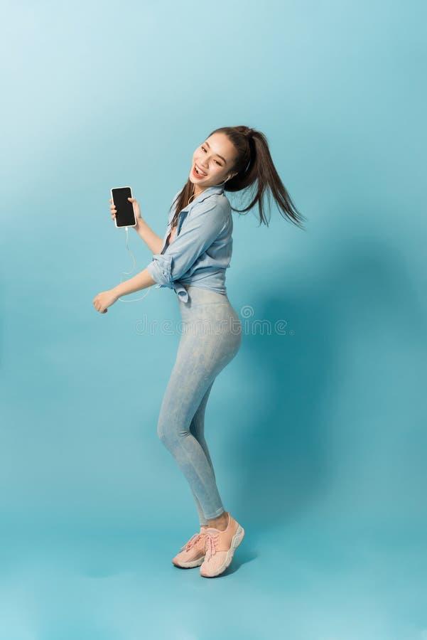 Vrolijk jong meisje die aan muziek met hoofdtelefoons luisteren terwijl het springen en het zingen over blauwe achtergrond stock foto's