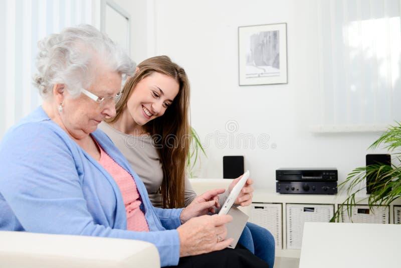 Vrolijk jong meisje die tijd met een oude hogere vrouw delen en Internet met een computertablet onderwijzen royalty-vrije stock afbeelding