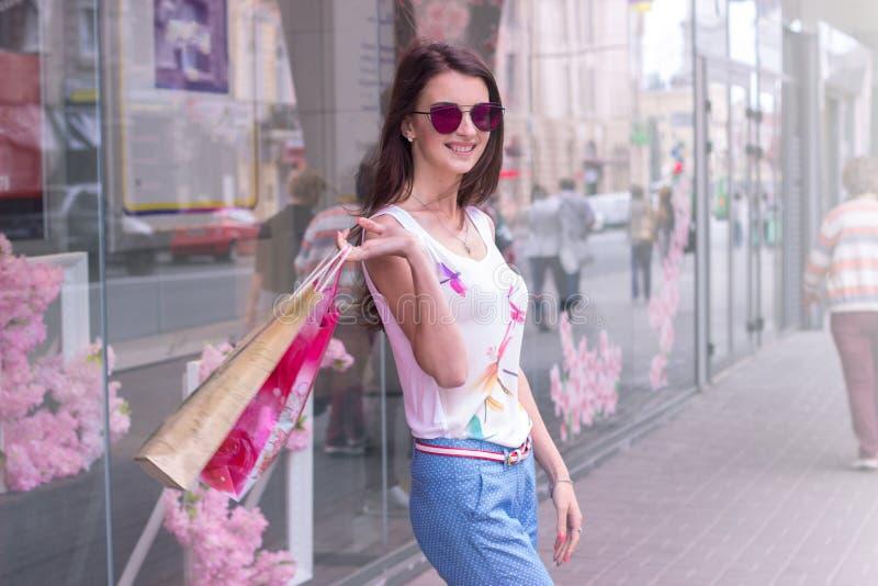 Vrolijk jong meisje met zakken in handenglimlachen op camera stock foto's