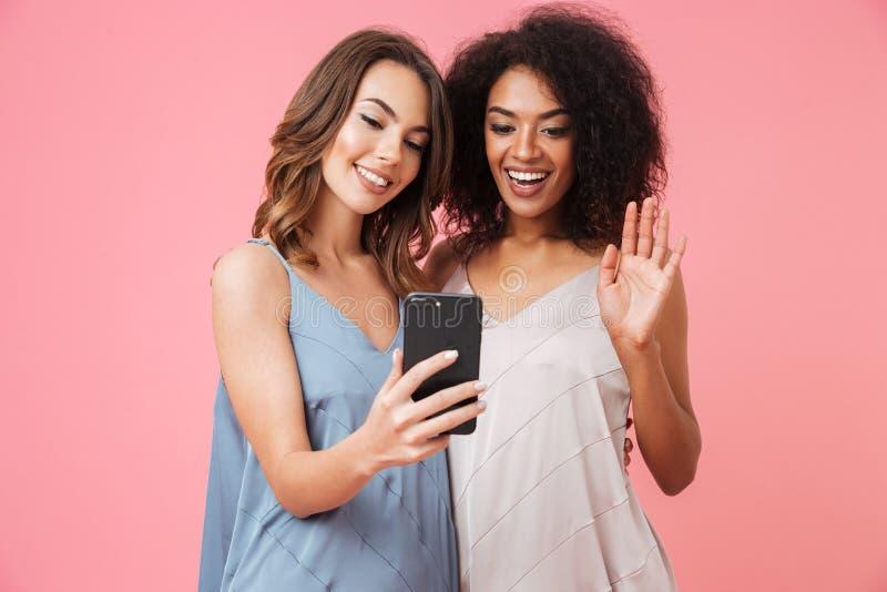 Vrolijk jong meisje twee die in kleding mobiele telefoon houden royalty-vrije stock foto