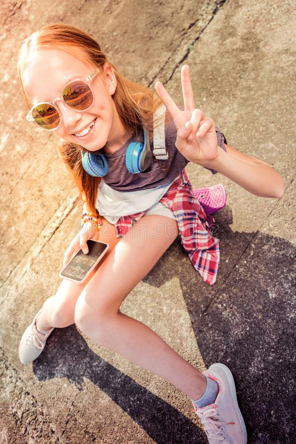 Vrolijk jong meisje in zonnebril die in grote stemming zijn terwijl buiten het blijven stock afbeelding