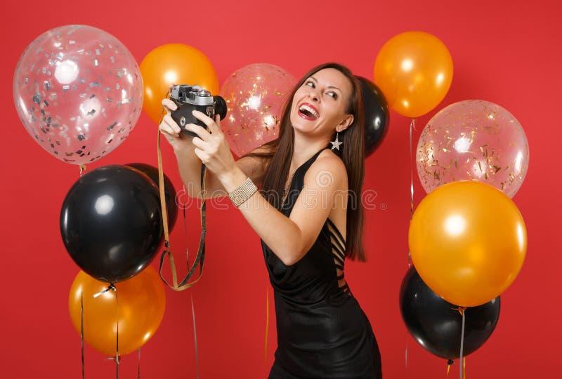 Vrolijk jong meisje in zwarte kleding die het nemen doen die selfie op retro uitstekende fotocamera wordt geschoten op heldere ro stock foto's
