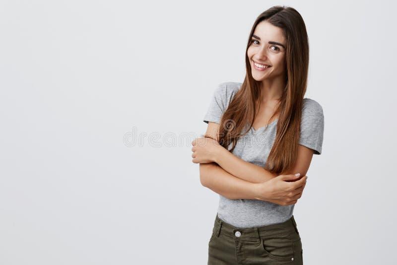 Vrolijk jong mooi donkerbruin Kaukasisch studentenmeisje die met lang haar in toevallige modieuze uitrusting helder glimlachen stock fotografie