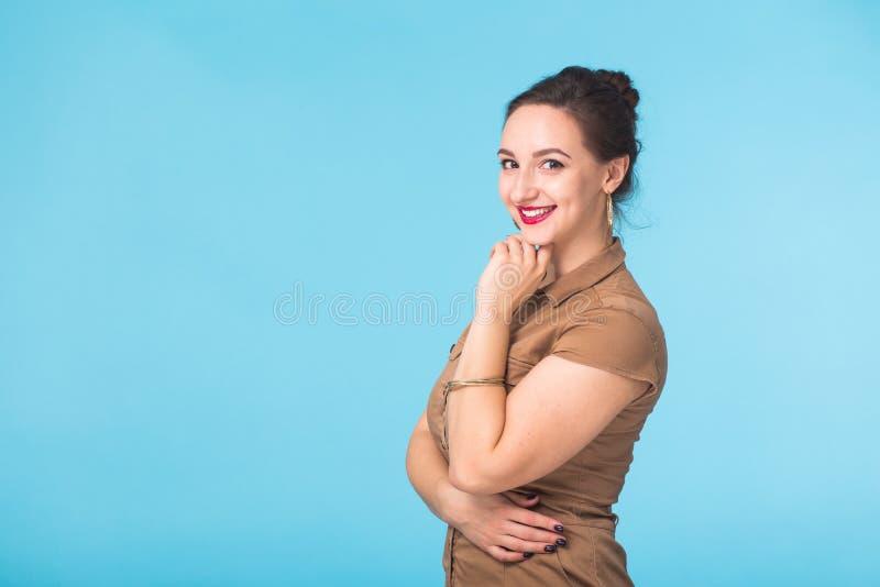 Vrolijk jong mooi donkerbruin Kaukasisch studentenmeisje die met lang haar in toevallige uitrusting helder op blauw glimlachen royalty-vrije stock foto