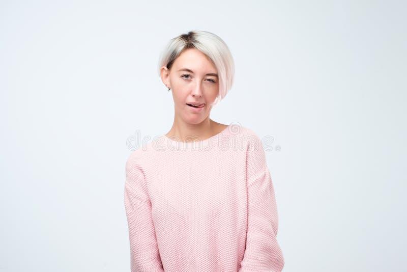 Vrolijk jong mooi meisje in het roze sweater glimlachen die tonend tong die camera bekijken knipogen stock foto