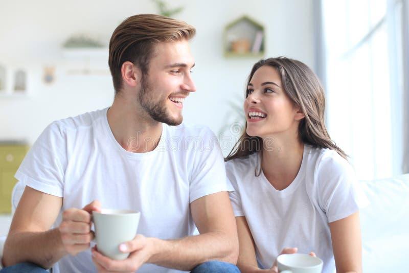 Vrolijk jong paar in de ochtend thuis in de woonkamer royalty-vrije stock afbeelding