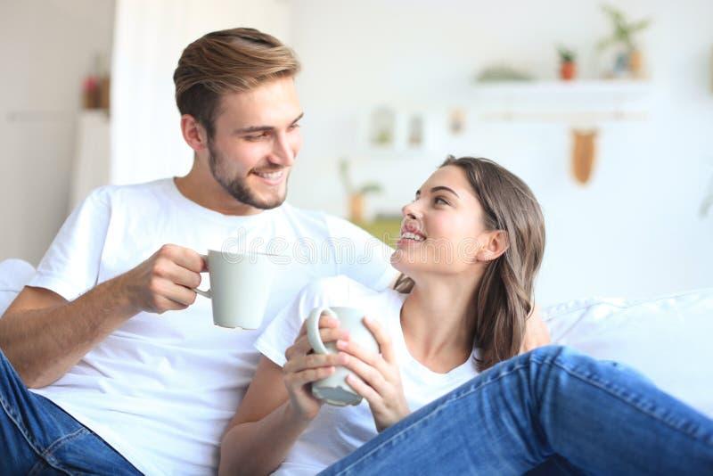 Vrolijk jong paar in de ochtend thuis in de woonkamer stock afbeeldingen