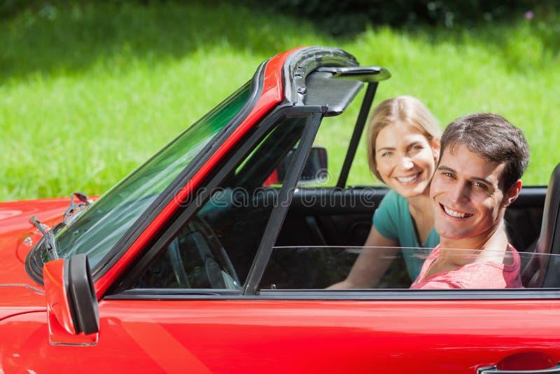Vrolijk jong paar die een rit in rode cabriolet hebben stock afbeelding