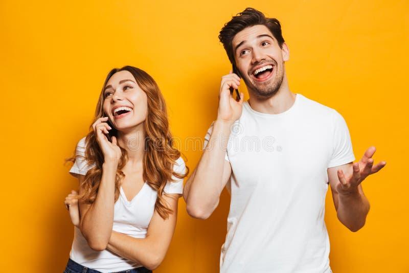 Vrolijk jong paar die op mobiele telefoons spreken stock afbeeldingen