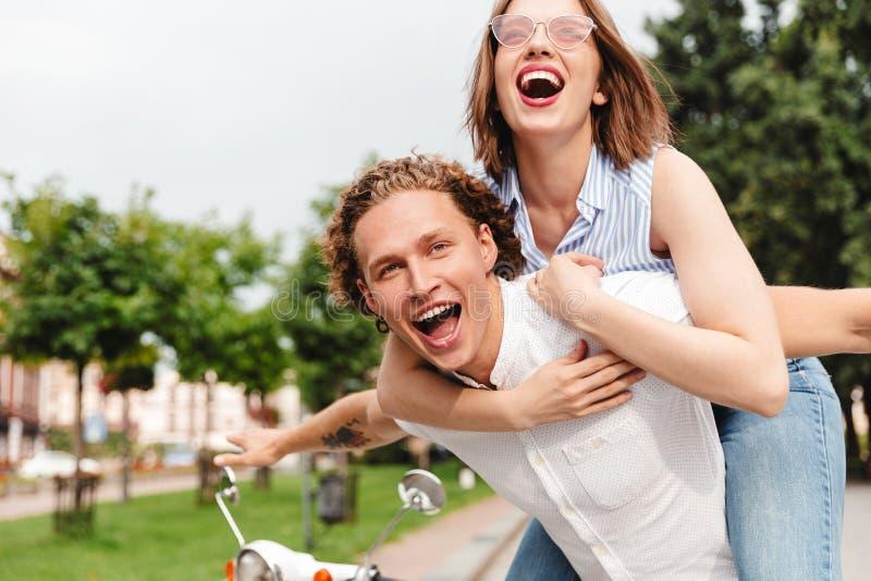 Vrolijk jong paar die pret samen met autoped hebben stock foto