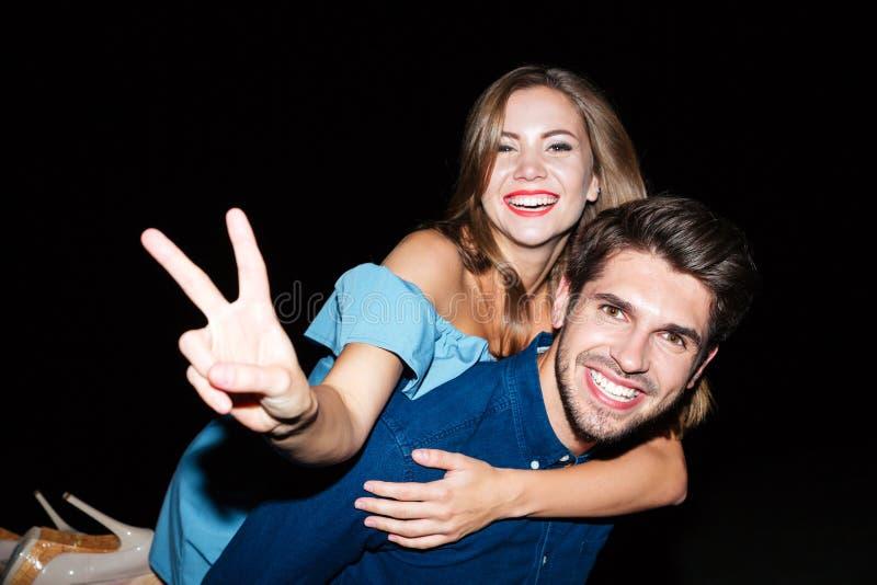 Vrolijk jong paar die vredesteken tonen en pret hebben royalty-vrije stock afbeeldingen