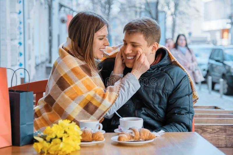 Vrolijk jong paar in openluchtkoffie die en pret hebben onder plaid lachen royalty-vrije stock foto