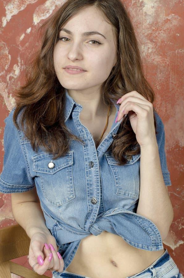 Vrolijk jong tienermeisje in denimborrels stock afbeeldingen