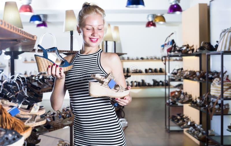 Vrolijk jong wijfje die van twee paren sandals kijken royalty-vrije stock afbeelding
