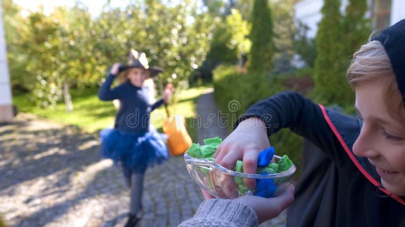 Vrolijk jongen en meisje in kostuums die suikergoed van plaat, gelukkige kinderjaren nemen stock fotografie