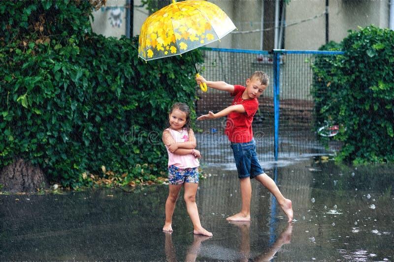 Vrolijk jongen en meisje met paraplu tijdens de zomerregen royalty-vrije stock afbeelding