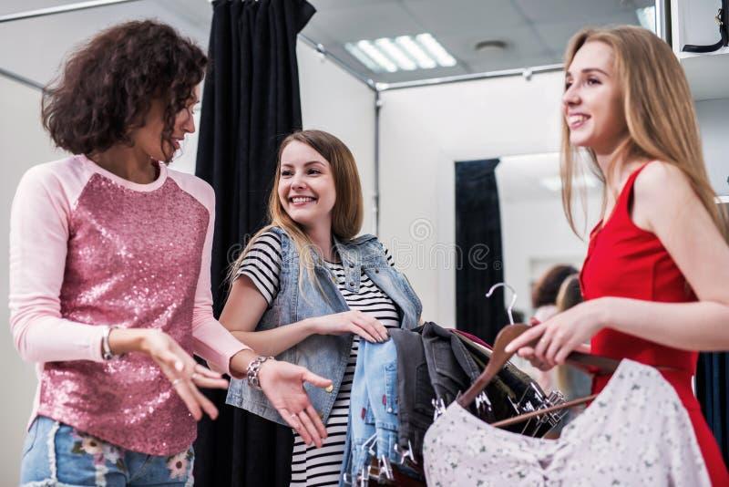 Vrolijk Kaukasisch meisje die of jeans met een winkelmedewerker kopen kiezen in een kledingsopslag stock fotografie