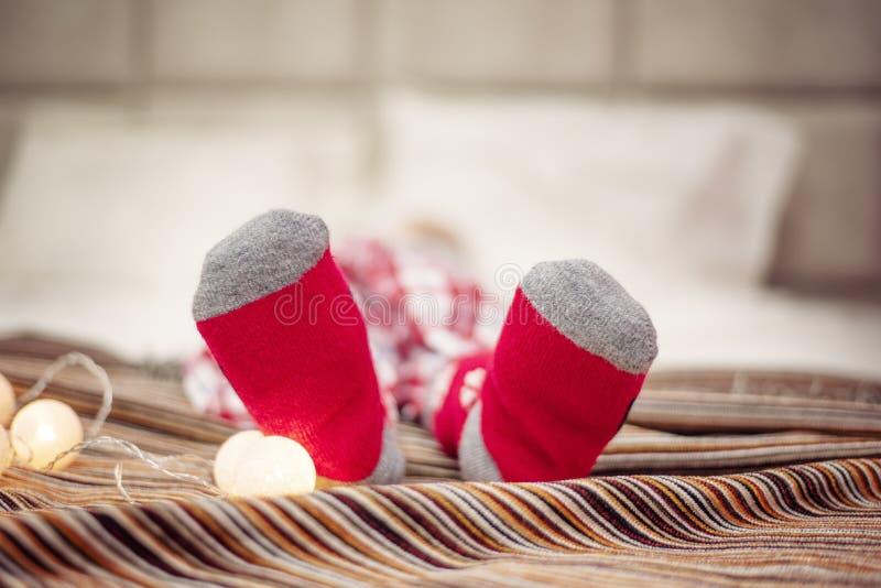 Vrolijk kerstfeest en vrolijke feestdagen Kindervoeten in rode sokken op bed Festive light garland background royalty-vrije stock afbeeldingen