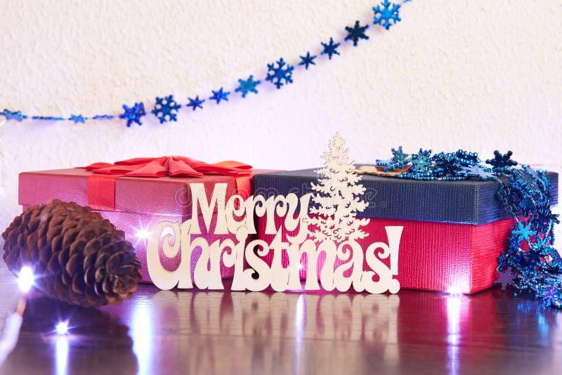 Vrolijk Kerstmis-Affiche of prentbriefkaarontwerp welke een houten inschrijving, juwelen, twee dozen van giften en een sparappel  royalty-vrije stock foto