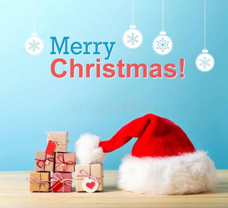Vrolijk Kerstmisbericht met een van de Kerstmanhoed en gift vakjes stock afbeelding