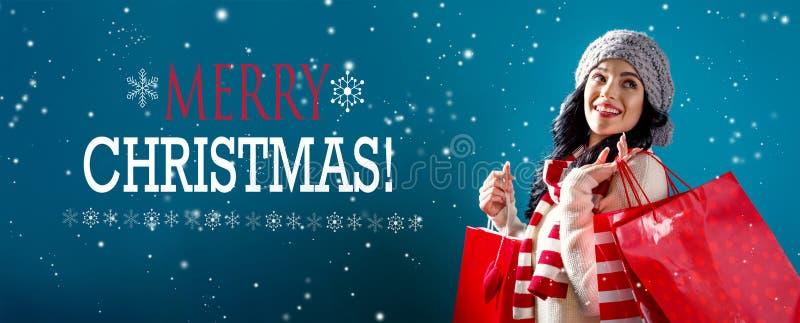 Vrolijk Kerstmisbericht met vrouwenholding het winkelen zakken stock foto