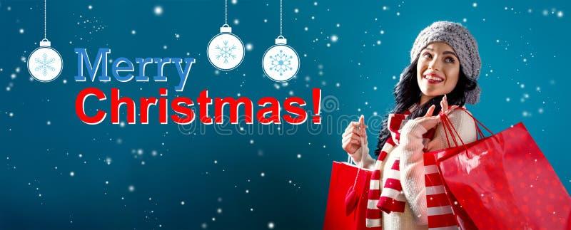 Vrolijk Kerstmisbericht met vrouwenholding het winkelen zakken royalty-vrije stock afbeeldingen