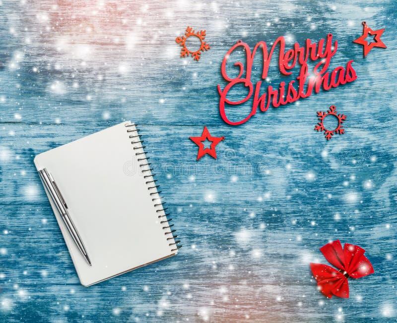 Vrolijk Kerstmisteken, met de hand gemaakt sparspeelgoed, met rood lint in hoeken en blocnote met pen voor tekstmening van hoogst royalty-vrije stock foto