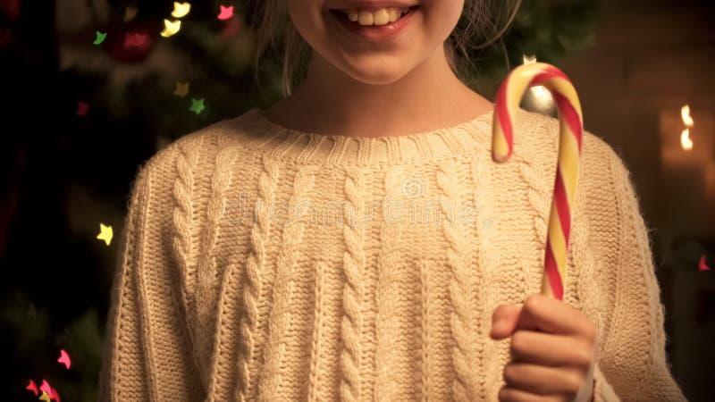 Vrolijk kind met het grote smakelijke suikergoedriet glimlachen, die bij camera, Kerstmis stellen royalty-vrije stock afbeeldingen