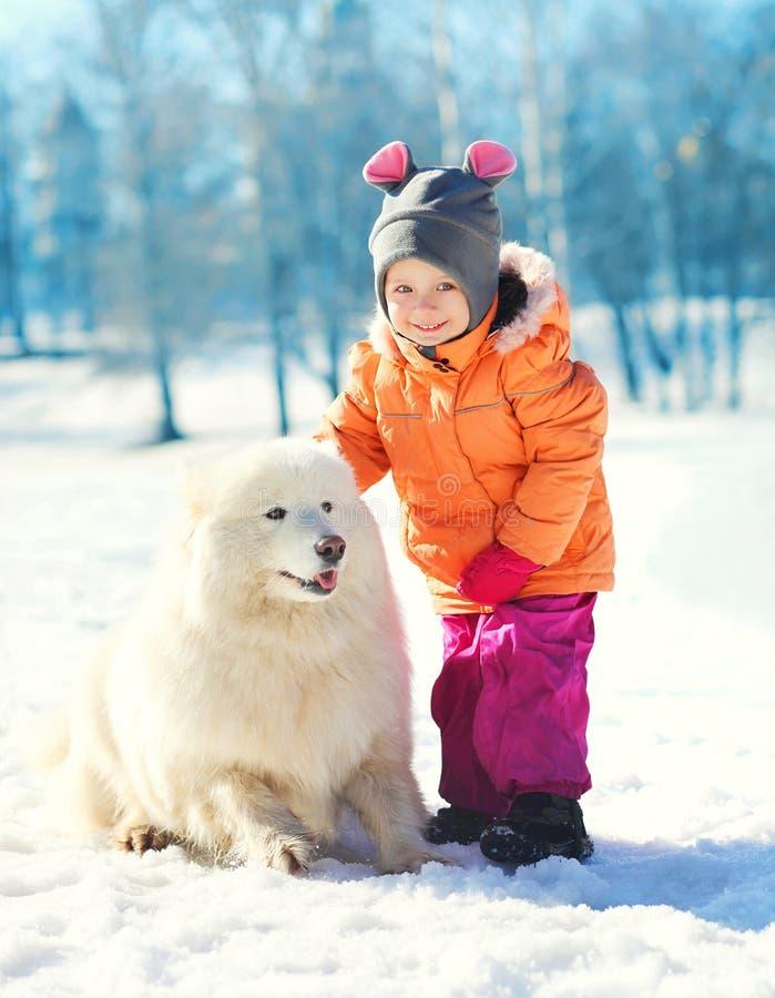 Vrolijk kind met witte Samoyed-hond op sneeuw in de winter stock afbeeldingen