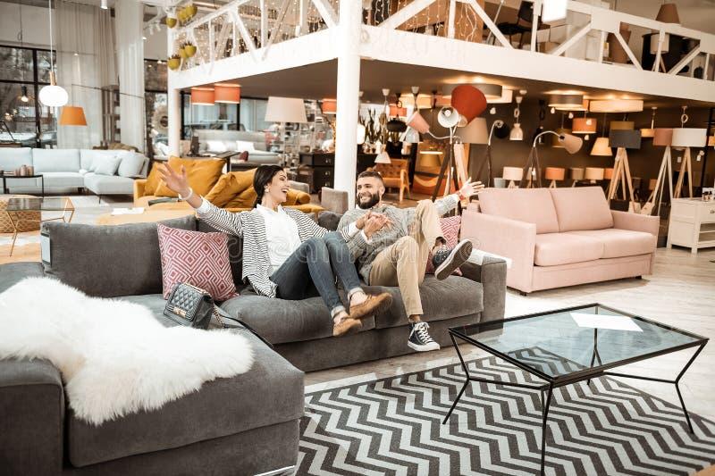 Vrolijk lachend paar die zich childishly in meubilairtoonzaal gedragen stock foto's