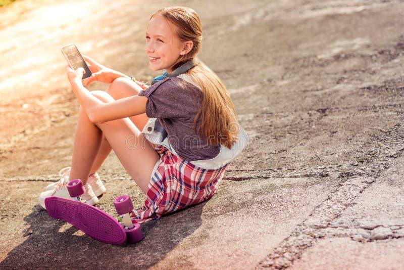 Vrolijk langharig meisje die ter plaatse met nabijgelegen skateboard blijven stock afbeelding