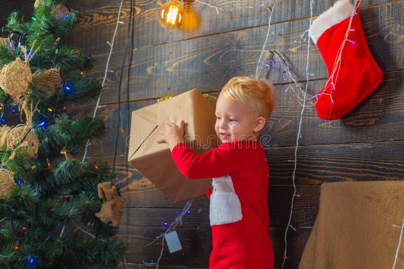 Vrolijk leuk kind die aanwezige Kerstmis openen Het openen van giften op Kerstmis en Nieuwjaar Grappige Kerstmis van de jong geit royalty-vrije stock foto